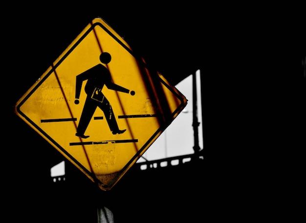 Panneau de passage pour piétons jaune avec ombre en milieu urbain
