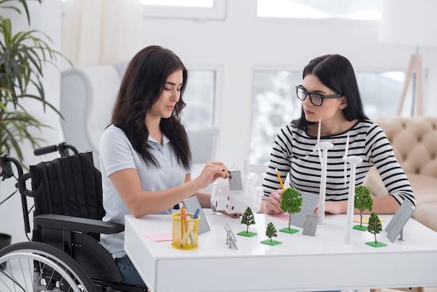 Panneau photovoltaïque. femme handicapée réfléchie et collègue discutant et travaillant avec des modèles d'énergie alternative