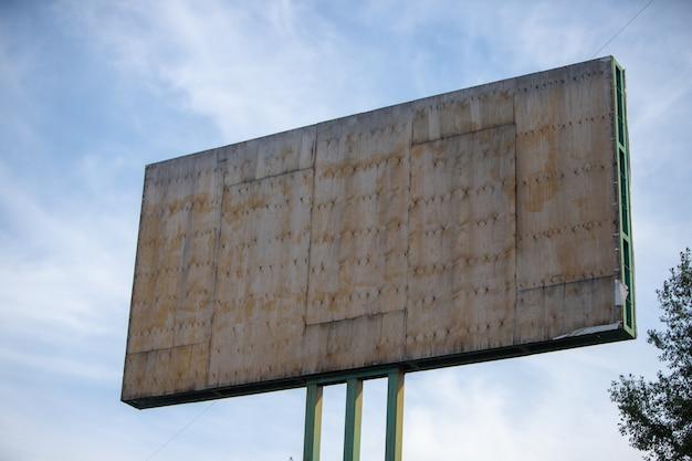 Panneau publicitaire pour la publicité sur un fond de ciel bleu et de couronnes d'arbres