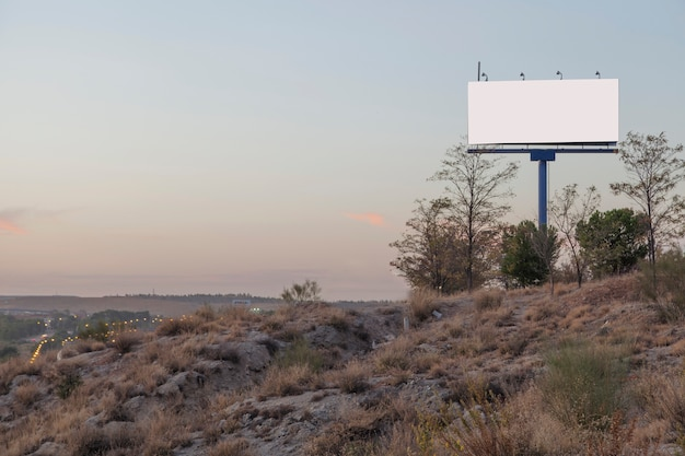 Un panneau publicitaire vide sur la montagne dans le ciel