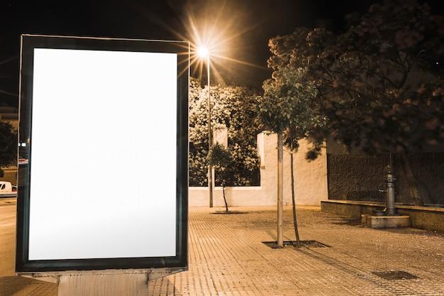 Panneau publicitaire vide près du réverbère éclairé