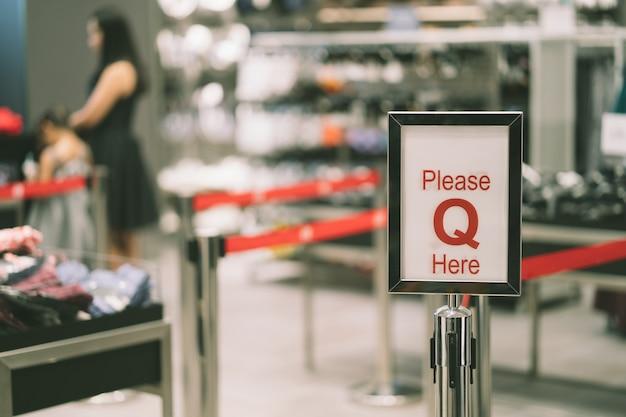 Panneau rouge avec texte s'il vous plaît faire la queue ici