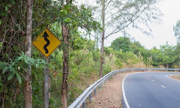 Panneau routier courbe ou ancien panneau routier sinueux à côté de la route de campagne vers quelque part au milieu de la forêt