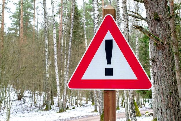 Panneau routier en forme triangulaire avec point d'exclamation en route forestière