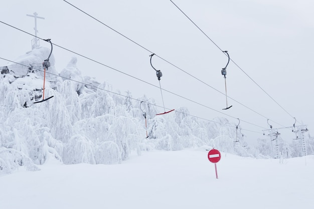 Panneau routier d'interdiction pas d'entrée dans le contexte d'un ski vide t-bar remontées mécaniques sur une piste de ski enneigée