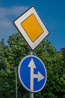 Panneau routier principal et flèches blanches sur fond bleu pointant tout droit, tournez à droite.