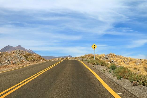 Panneau routier sinueux sur la route du désert vide du désert d'atacama, chili