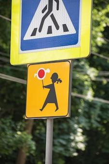 Panneau de signalisation attention les enfants. poteau indicateur. femme avec des bonbons.