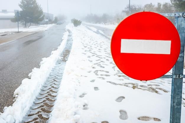 Panneau de signalisation de direction interdite sur une route enneigée en hiver.