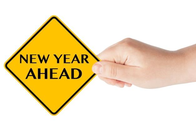 Panneau de signalisation du nouvel an à venir dans la main de la femme sur fond blanc