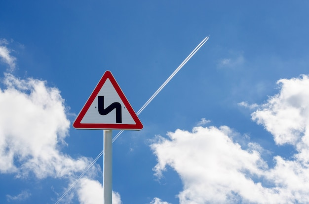 Panneau de signalisation sur fond de ciel. la trace de l'avion