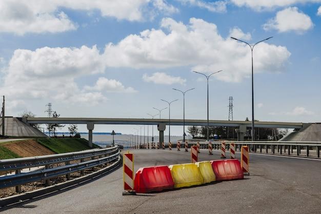 Panneau de signalisation rouge et blanc, barrières de guidage routier s'alignent sur la route