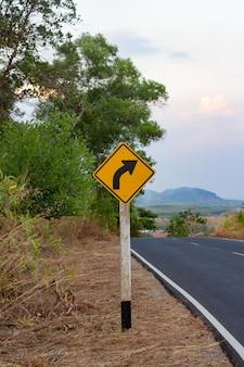 Panneau de signalisation sinueux à côté de la route de campagne