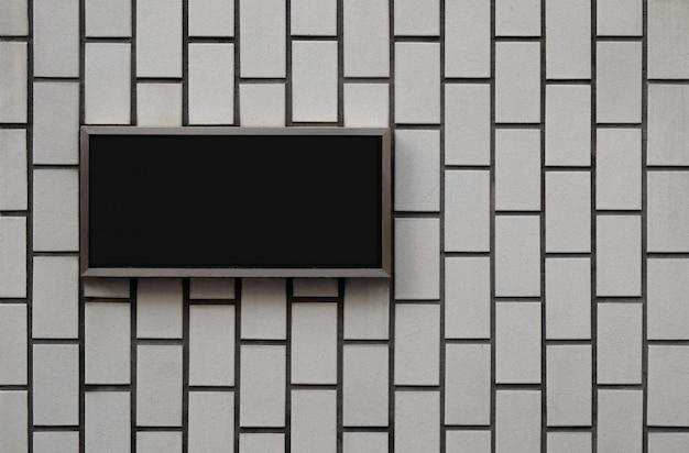 Panneau de signalisation vierge noir sur la texture du mur