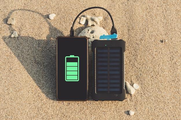 Le panneau solaire portable est sur la plage dans le sable et charge la batterie du téléphone portable sans cadre. utilisation de l'énergie solaire à l'état sauvage sur une île déserte
