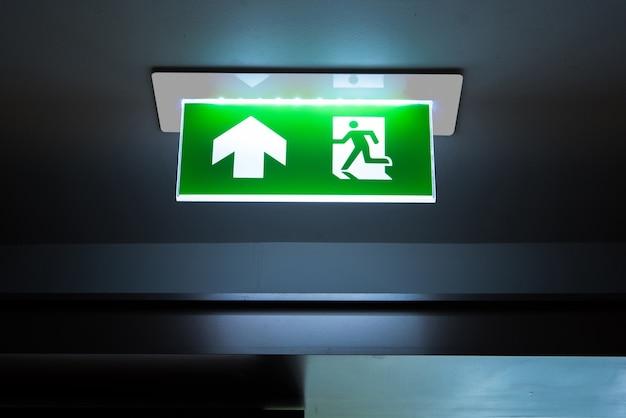 Panneau de sortie de secours vert indiquant le chemin pour s'échapper.