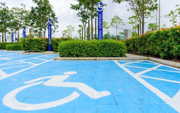 Panneau de stationnement pour personnes handicapées bleu dans la zone du parking.