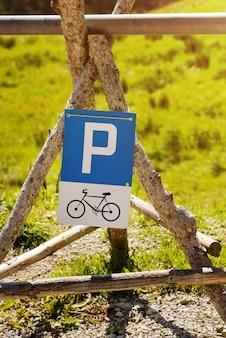 Panneau de stationnement pour vélos monté sur des poteaux en bois.