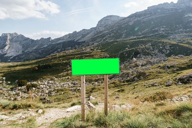 Panneau vierge rectangulaire sur le bord de la route avec des montagnes dans la surface