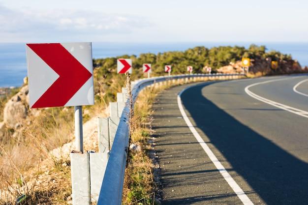 Panneau de virage à droite: les panneaux de signalisation signalent un virage serré sur une route étroite.
