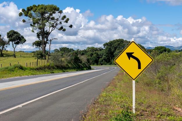Panneau de virage à gauche sur la route avec un paysage magnifique