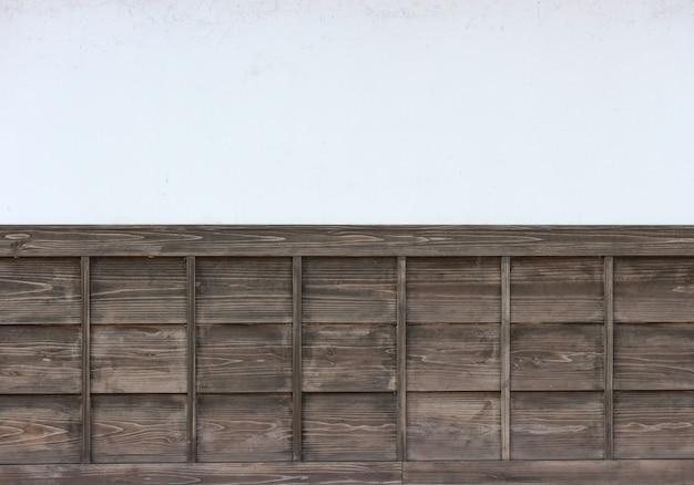 Panneaux de bois bruns vieux style japonais sur fond de mur de ciment blanc.
