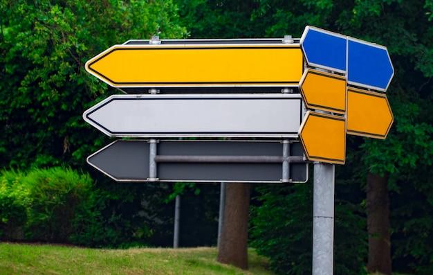 Panneaux routiers directionnels vierges contre parc. flèches métalliques sur le panneau.