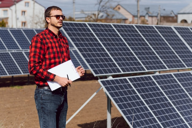 Panneaux solaires et un homme debout près de panneaux solaires
