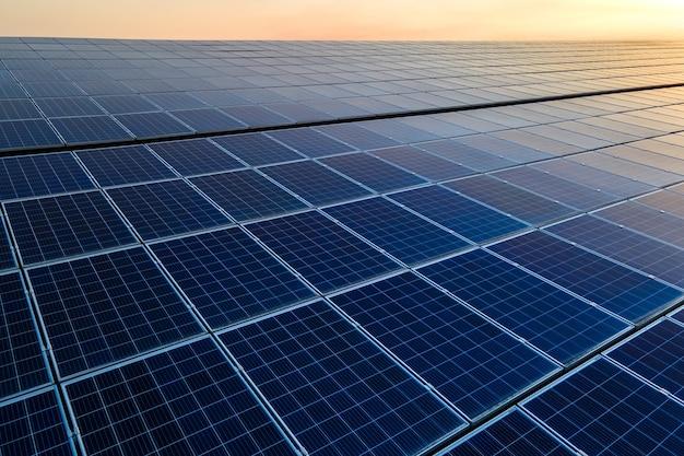 Panneaux solaires photovoltaïques bleus montés sur le toit du bâtiment pour produire de l'électricité écologique propre au coucher du soleil. production de concept d'énergie renouvelable.