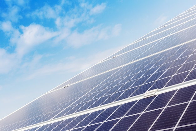 Panneaux solaires sur le toit de la maison contre le ciel bleu. centrale à énergie solaire. technologie de l'électricité solaire. stock photo panneaux solaires en journée ensoleillée.