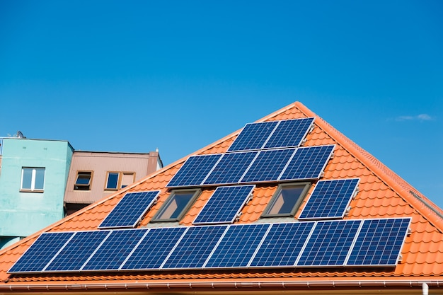 Panneaux solaires sur le toit rouge d'un immeuble