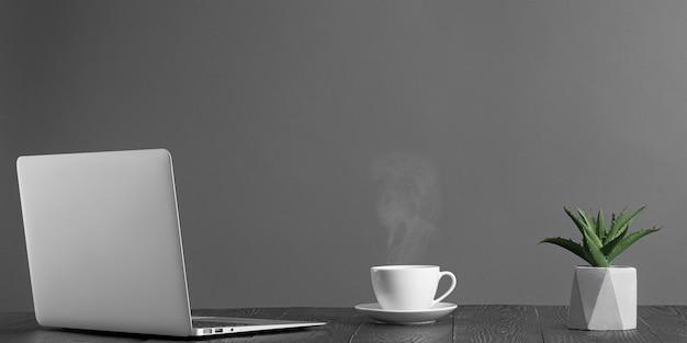 Un panorama de bureau avec ordinateur portable et café pour la publicité