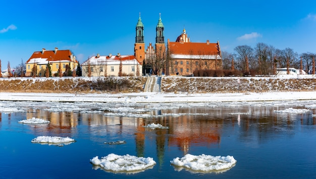 Panorama de la cathédrale de poznan et la dérive de glace sur la rivière warta dans la journée ensoleillée d'hiver, poznan