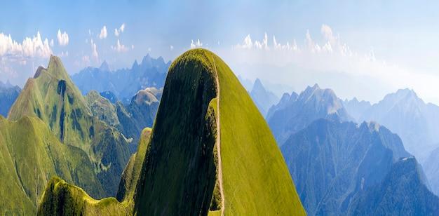 Panorama des collines verdoyantes dans les montagnes d'été avec route de gravier pour voyager en voiture