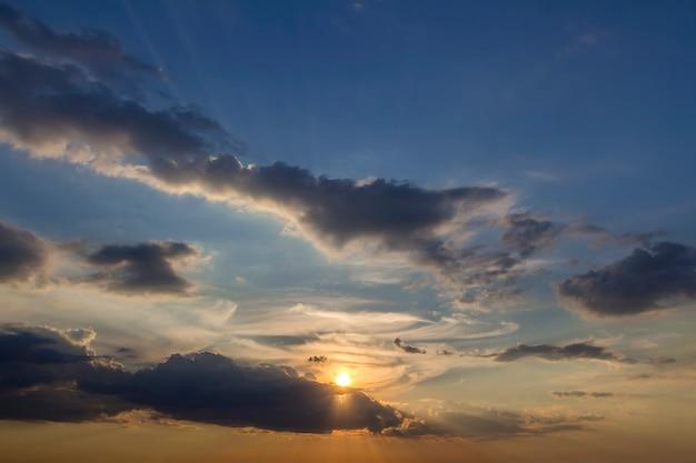 Panorama du ciel au lever ou au coucher du soleil. belle vue sur les nuages bleu foncé éclairés par le soleil jaune orange vif sur ciel clair.