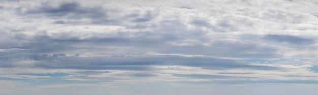 Panorama du ciel bleu avec des nuages blancs et gris denses