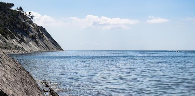 Panorama du paysage marin. une plage sauvage en pierre pittoresque au pied des falaises et un ciel bleu éclatant avec des nuages.