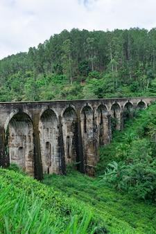 Panorama du pont à neuf arches, situé dans la jungle profonde de demodara, par temps nuageux, ella, sri lanka