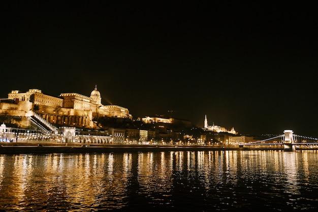 Panorama de l'ensemble du palais royal avec un pont sur le danube à budapest la nuit avec