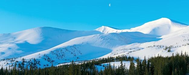 Panorama de montagne du matin avec de longues ombres de l'aube bleu et lune dans le ciel