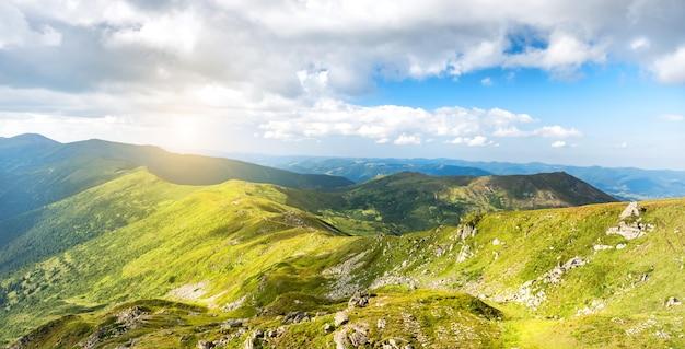 Panorama des montagnes et coucher de soleil avec pics, rochers et nature verdoyante