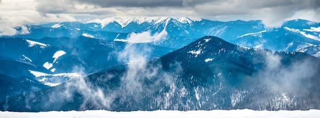 Panorama des montagnes d'hiver dans la neige. paysage avec un temps dramatique