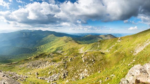 Panorama des montagnes avec des pics, des rochers et une nature verdoyante
