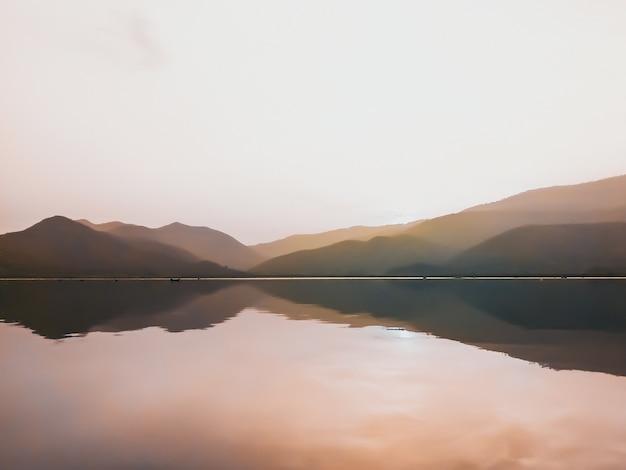 Panorama panoramique du magnifique coucher de soleil au bord du lac avec des chaînes de montagnes sur fond. nature minimale.