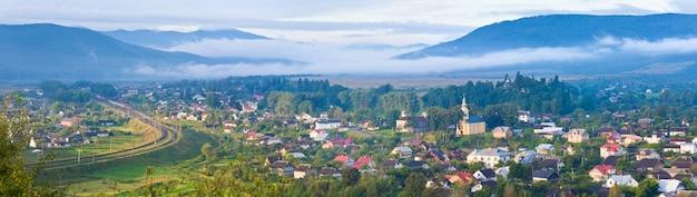 Panorama de pays brumeux d'été (village de werchnie syniowydne, skole raion, oblast de lviv, ukraine) . trois clichés piquent l'image.