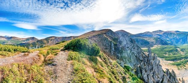 Panorama avec paysage de montagnes, rochers, herbe sèche et ciel bleu