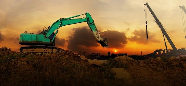 Panorama de la pelle travaillant sur un chantier de construction au coucher du soleil