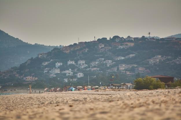 Panorama avec petite montagne pleine de maisons donnant sur la plage avec quelques touristes à l'horizon