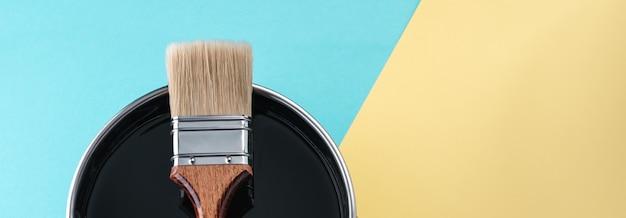 Panorama d'un pinceau sur le pot de peinture sur fond jaune et bleu avec espace de copie