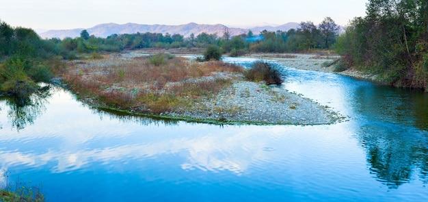 Panorama de la rivière bleue et montagne de soirée d'automne derrière. quatre clichés piquent l'image.